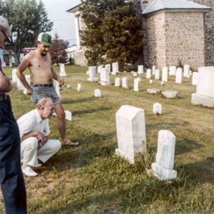 "The late John (""Jack"") Robinson, of Severna Park, Maryland, accompanied by others, including his late first cousin from California, the Reverend Dr. Ross Banes Anderson, Jr., of California, is shown inspecting and reading the monumented grave stone at the Wards Chapel United Methodist Church near Randallstown in Baltimore County, Maryland, of the Reverend Dr. Ross Banes Anderson, Jr.'s late grandfather, Civil War Veteran Richard Thomas Anderson, on an occasion in fairly recent years before that monumented grave stone was erroneously thought to have been disturbed and removed, without permission, in more recent years. (In fact, the partial image of the Reverend Dr. Ross Banes Anderson, Jr., appears, standing to the left of, and slightly in front of, the full image of his first cousin, Jack Robinson, squatting, in this particular photograph. One can distinguish Dr. Anderson's hat or cap and his eye glasses in the extreme left hand side of this photo image.)"